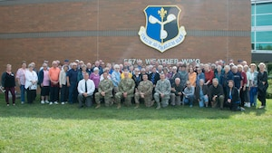 Visitors from Rochester, Minnesota, pose for a group photo with members of the 557th Weather Wing in front of the 557th WW headquarters building at Offutt Air Force Base, Nebraska, Sept. 19, 2019. Members of the group annually bake cookies for care packages sent to deployed service members. (U.S. Air Force photo by Paul Shirk)