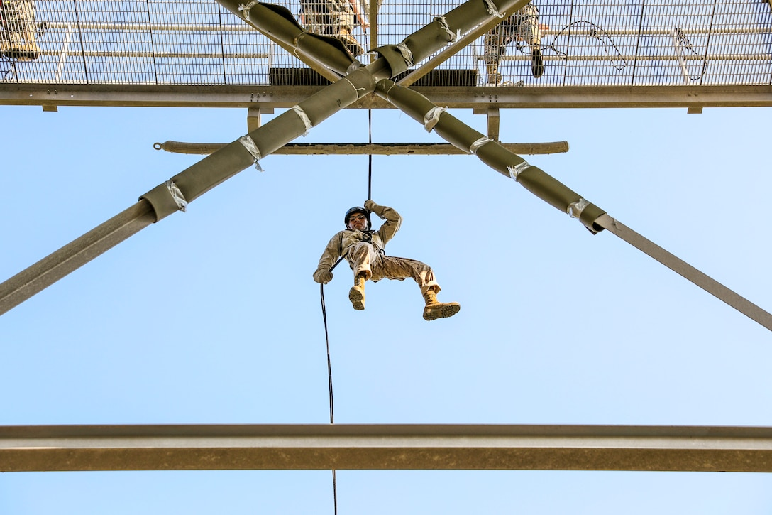 A Marine suspended from a rope hangs mid-air between triangular beams.