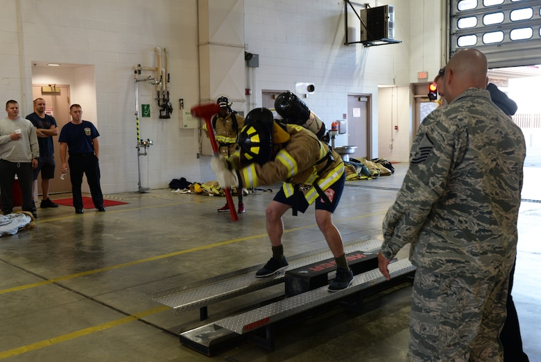 An Airman hits a keiser sled during the Firefighter Challenge at the 28th Civil Engineer Squadron Fire Department at Ellsworth Air Force Base, S.D., Oct. 4, 2019. Hitting a keiser sled simulates trying to bust down drywall or a hard wall during a house fire. (U.S. Air Force photo by Airman Quentin K. Marx)