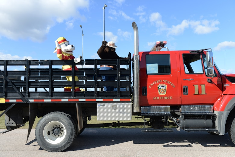 """Sparky the Dalmatian and Smoky the Bear wave to children during the Fire Prevention Week Parade at the Prairie View housing area at Ellsworth Air Force Base, S.D., Oct. 5, 2019. Five fire trucks from the 28th Civil Engineer Squadron Fire Department drove through base housing during the parade and promoted Fire Prevention Week, which commemorates the """"Great Chicago Fire"""" from 1871. (U.S. Air Force photo by Airman Quentin K. Marx)"""