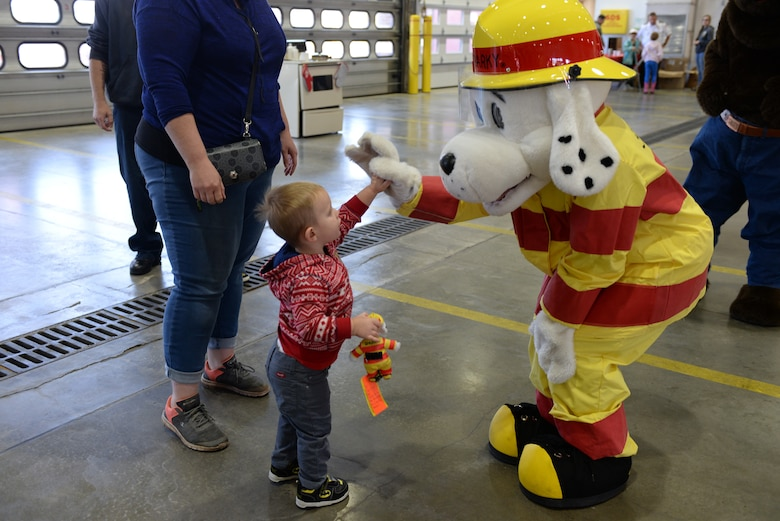 Sparky the Dalmatian high-fives a child during the Fire Prevention Week Open House event at the 28th Civil Engineer Squadron Fire Department at Ellsworth Air Force Base, S.D., Oct. 5, 2019. The Fire Department conducted an open house where children and families could interact with Sparky and learn fire safety. (U.S. Air Force photo by Airman Quentin K. Marx)