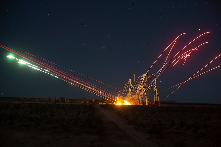 Red, green and orange lights streaked across the sky at night.
