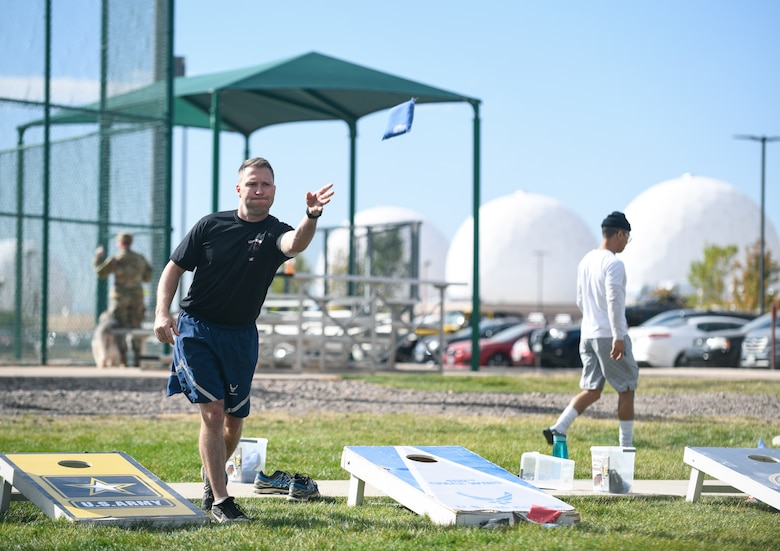 Senior Master Sgt. Michael Grosebeck, the 460th Wing Staff Agency superintendent, throws a bean bag during a game of cornhole at the softball fields on Buckley Air Force Base, Colo.