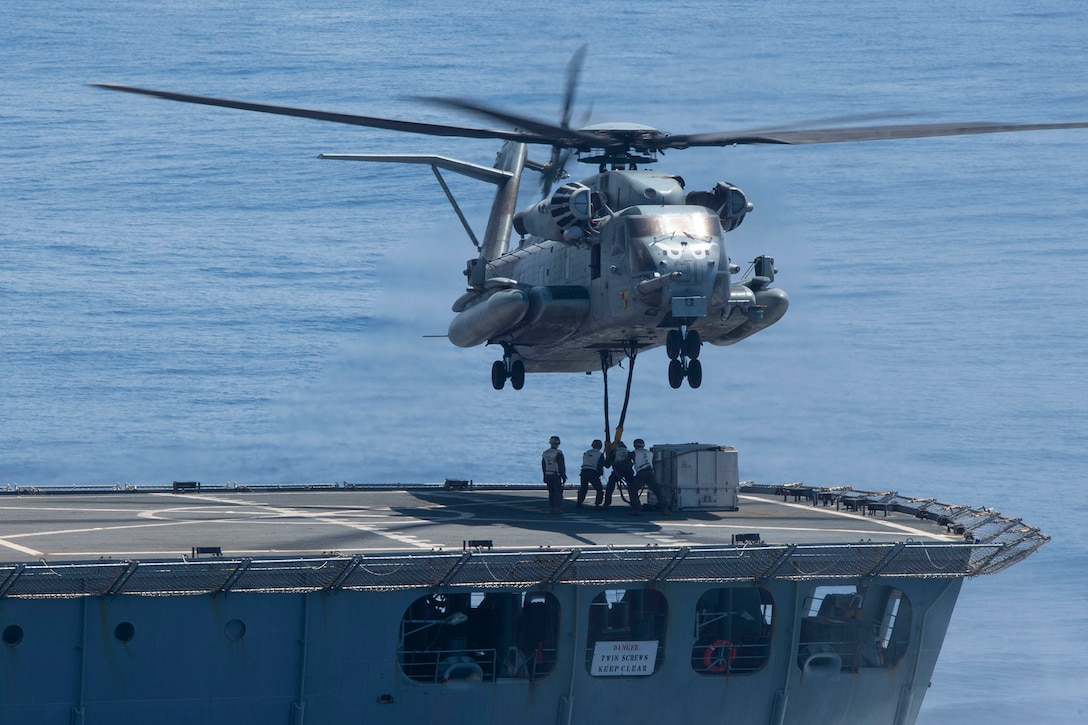 Marines stand on a ship's deck attaching cargo to a helicopter flying above.