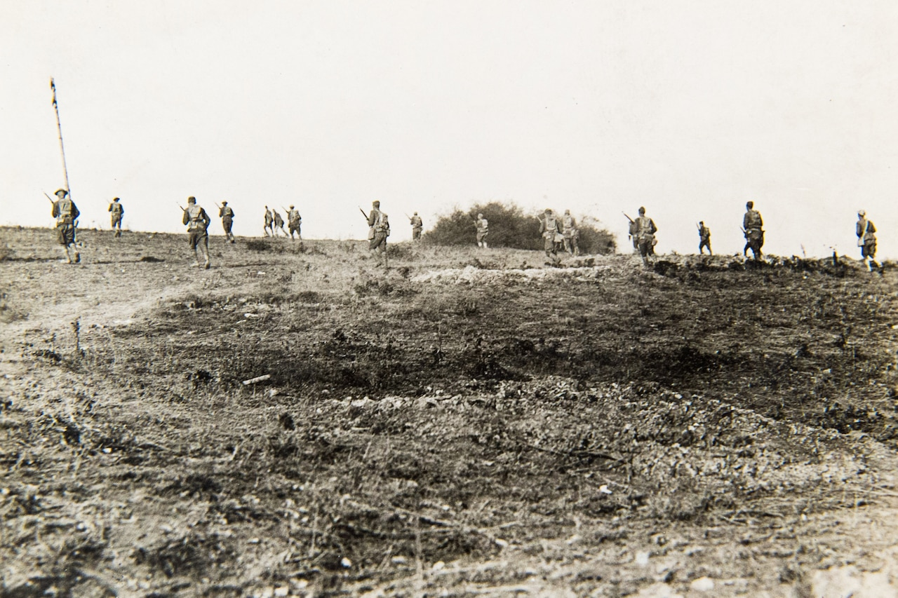 Several soldiers in the distance run away from the camera in what appears to be a burned-out, barren wasteland.
