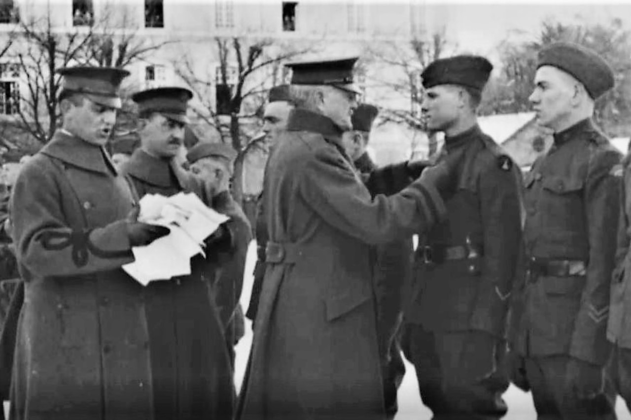 An Army general pins the Medal of Honor to the chest of a soldier as a few other soldiers stand in line to also receive the honor.