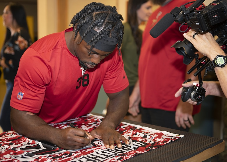 Kenjon Barner, Atlanta Falcons running back, signs memorabilia during a tour of the 56th Operations Support Squadron Aircrew Flight Equipment's facility Oct. 8, 2019, at Luke Air Force Base, Ariz.