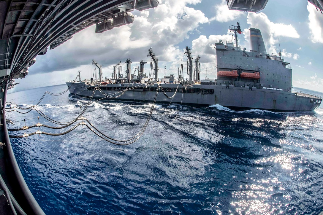 Fuel lines extend from one ship to another as they travel in blue waters.