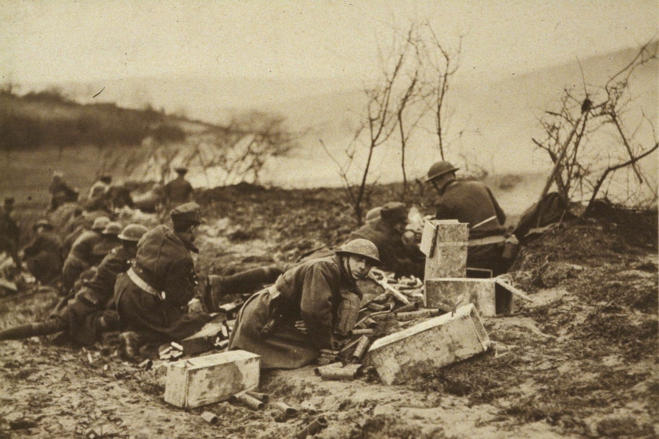 World War I soldiers ducking down low are surrounded by large cartridges as they battle in a barren wasteland. Smoke can be seen in the distance. One soldier looks directly at the camera.