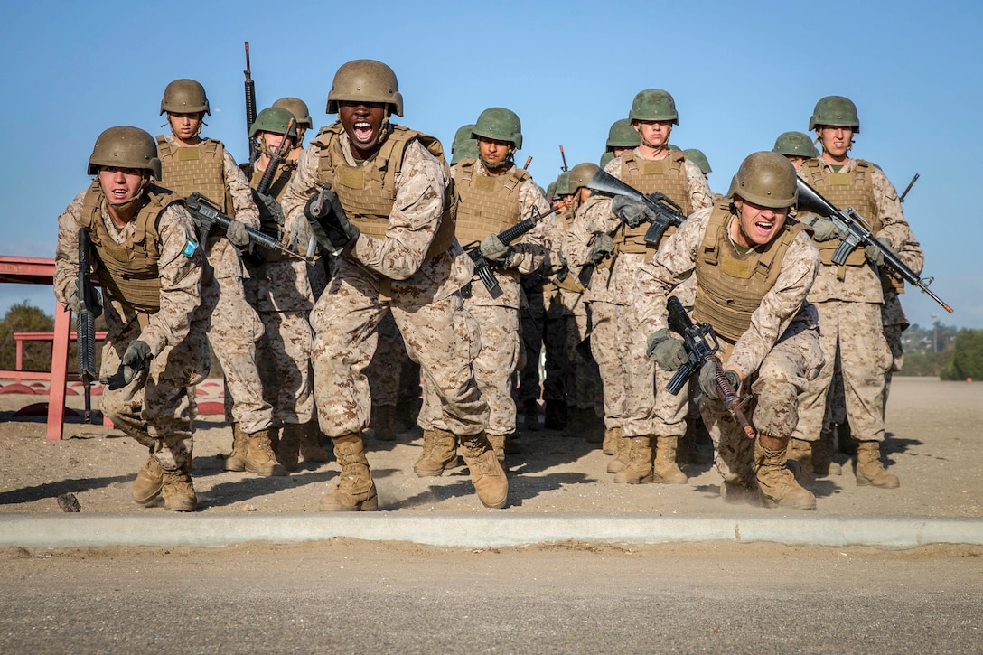 Marines in helmets wielding rifles charge forward on an outdoor course while yelling.
