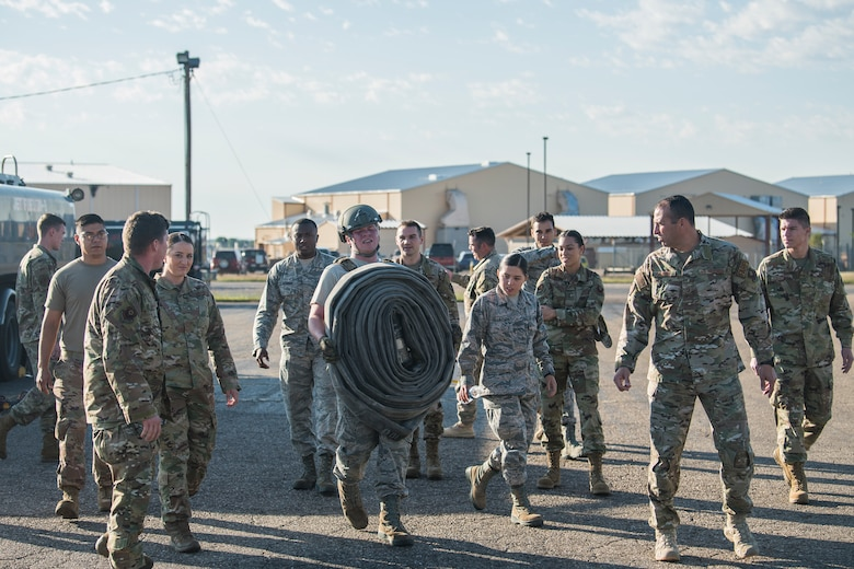 Airman 1st Class Kyle Fabrizius, 27th Special Operations Logistics Readiness Squadron fuels distribution technician, carries a fuel hose while members of the 27 SOLRS watch and cheer him on during the Forward Air Refueling Point tryouts at Cannon Air Force Base, N.M., October 9, 2019. The hose carry is the final part of the tryout, where members have to carry a 100 pound hose as fast as they can. (U.S. Air Force photo by Senior Airman Vernon R. Walter III)