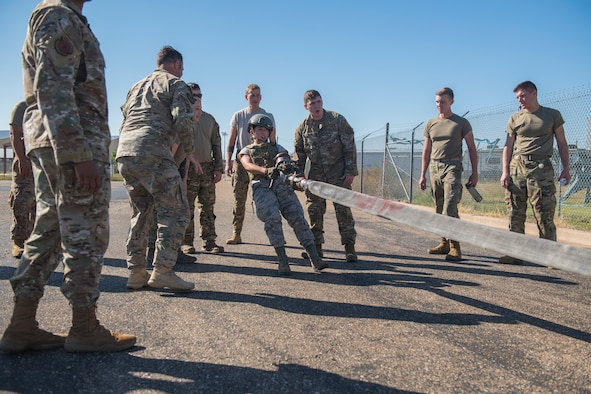 Airman Basic Sarah De La Rosa, 27th Special Operations Logistics Readiness Squadron fuels technician, drags a fuel hose as her team encourages her during the Forward Air Refueling Point tryouts at Cannon Air Force Base, N.M., October 9, 2019. The hose dragging is meant to simulate dragging a hose to an awaiting aircraft. (U.S. Air Force photo by Senior Airman Vernon R. Walter III)