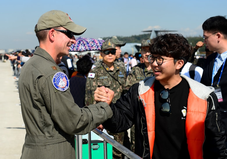 "U.S. Air Force Maj. Dan ""Rock"" Dickinson, Air Combat Command F-22 Raptor Demonstration Team pilot, shakes the hand of an enthusiastic fan after his performance at the Seoul International Aerospace and Defense Exhibition 2017 at the Seoul Airport, Republic of Korea, Oct. 20, 2017. The Seoul ADEX is the largest, most comprehensive event of its kind in Northeast Asia, attracting aviation and aerospace professionals, key defense personnel, aviation enthusiasts and the general public alike. (U.S. Air Force photo by Staff Sgt. Alex Fox Echols III)"