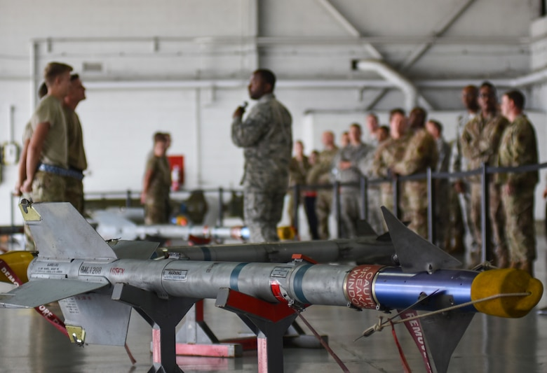 Weapons load crew members assigned to the 20th Aircraft Maintenance Squadron and spectators gather to watch a quarterly load crew competition at Shaw Air Force Base, South Carolina, Oct. 7, 2019.