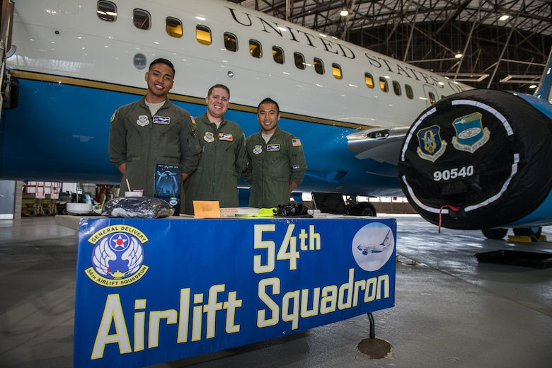 Crew from the 54th Airlift Squadron, pilots  Maj. Andrew Floro, right, Maj. Neal Brinkworth, center, and executive flight attendant Senior Airman DJ Ramones, take a photo moment before giving tours of the 932nd Airlift Wing C-40 aircraft and sharing their Air Force careers with nearly 400 visiting JROTC high students from Missouri and Illinois, Oct. 8, 2019, Scott Air Force Base, Illinois. (U.S. Air Force photo by Christopher Parr)