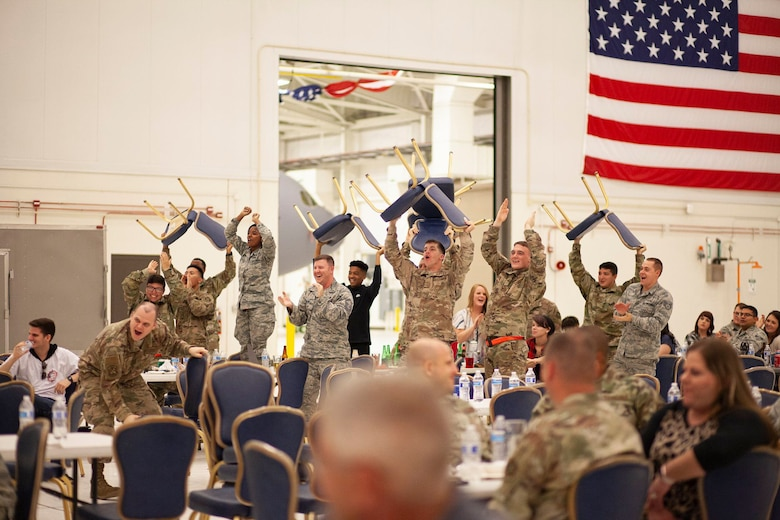A group of maintainers from the 22nd Maintenance Squadron, celebrate as a fellow Airman receives an award during the Knucklebuster's Award Ceremony Oct. 5, 2019, at McConnell Air Force Base, Kan. A total of 35 awards were given during the banquet.  (U.S. Air Force photo by 2nd Lt. Kaitlyn Danner)