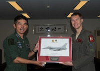 Japan Air Self-Defense Force Maj. Gen. Masahito Monma, the Japan Air Self-Defense Force 6th Air Wing commander, and U.S. Air Force Capt. Phillip McCoy, a 13th Fighter Squadron F-16 Fighting Falcon pilot, poses for a photo with an F-16 framed photo during an aviation training relocation at Komatsu Air Base, Japan, Sept. 30, 2019. McCoy presented Monma this item as a gift to express his gratitude toward JASDF's hospitability, support and friendship. (U.S. Air Force photo by Senior Airman Collette Brooks)