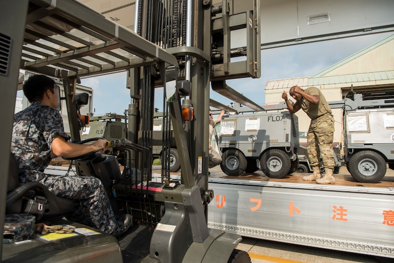 U.S. Air Force Staff Sgt. Edwin Long, a 35th Logistic Readiness Squadron traffic management office outbound cargo supervisor, gives a Japan Air Self-Defense Force member a thumbs up while unloading cargo during an aviation training relocation at Komatsu Air Base, Japan, Sept. 30, 2019. During the week-long exercise, participants facilitated F-16 maintenance training, communication practice and bilateral maintenance equipment sharing. (U.S. Air Force photo by Senior Airman Collette Brooks)
