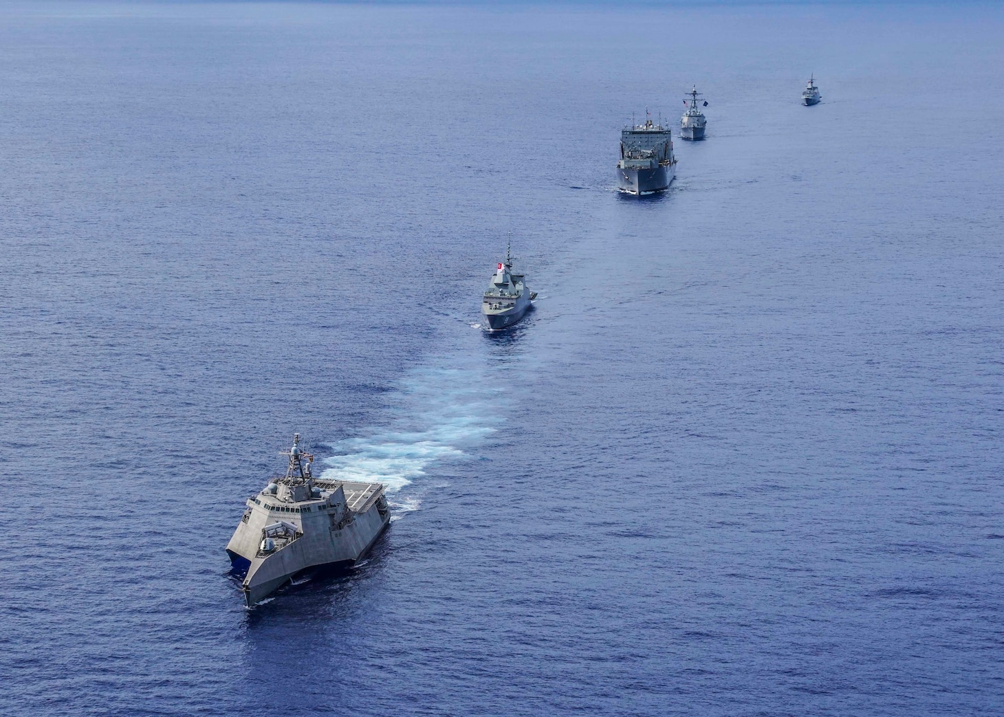 WATERS NEAR GUAM (Sept. 30, 2019) The littoral combat ship USS Gabrielle Giffords (LCS 10) leads a formation followed by Republic of Singapore Navy (RSN) frigate RSS Formidable (FFS 68), dry cargo ship USNS Amelia Earhart (T-AKE 6), guided-missile destroyer USS Momsen (DDG 92), and RSN frigate RSS Intrepid (FFS 69) during a photo exercise (PHOTOEX) in support of Exercise Pacific Griffin 2019. Pacific Griffin is a biennial exercise conducted in the waters near Guam aimed at enhancing combined proficiency at sea while strengthening relationships between the U.S. and Republic of Singapore navies.