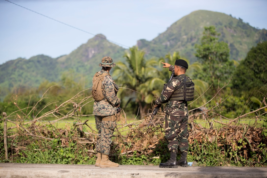 "Philippine Air Force Airman Junnevee Cuenca points out a terrain feature to U.S. Marine Lance Cpl. Tatyana Saldana during KAMANDAG 3 at Colonel Ernesto P. Ravina Air Base, Philippines, Oct. 9, 2019. The specific objectives of KAMANDAG, such as mutual defense, counterterrorism, and humanitarian assistance and disaster relief, promote realistic training that supports regional security. Cuenca, a native of Zamboanga City, Philippines, is a combat air controller with 710th Special Operations Wing. Saldana, a native of Tallulah, La., is a military policeman with 3rd Law Enforcement Battalion. KAMANDAG 3 is a Philippine-led, bilateral exercise with participation from Japan. KAMANDAG is an acronym for the Filipino phrase ""Kaagapay Ng Mga Manirigma Ng Dagat,"" which translates to ""Cooperation of the Warriors of the Sea,"" highlighting the partnership between the U.S. and Philippine militaries."