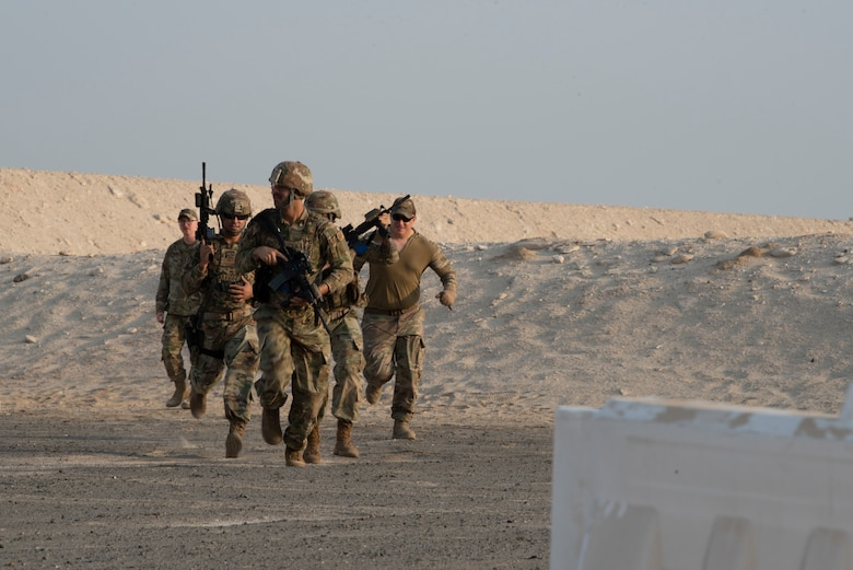 380th Expeditionary Security Forces Squadron Airmen run toward a barrier to take cover during a simunition proficiency firing course held on Al Dhafra Air Base, United Arab Emirates, Sept. 29, 2019.