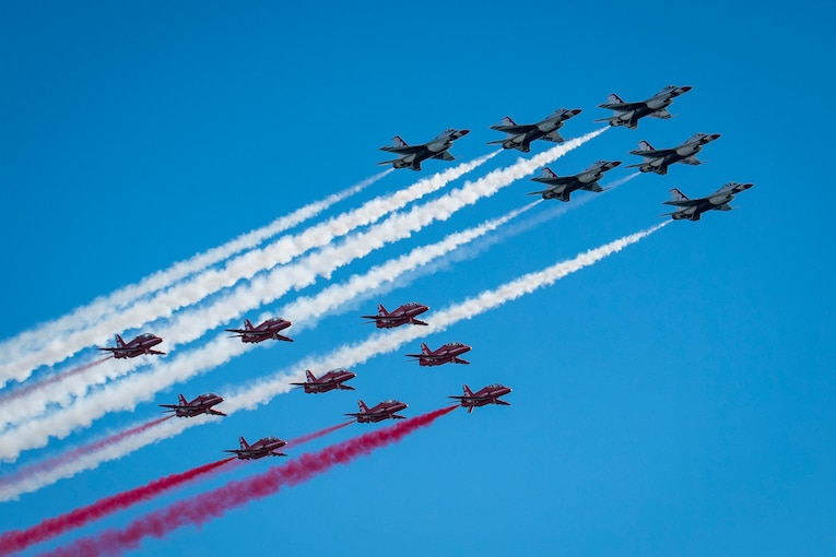 Two groups of military jets fly across a blue sky trailing red and white smoke.