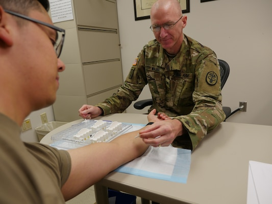 Army Col. (Dr.) Kirk Waibel, allergist/immunologist, prepares to give a mountain cedar allergy test to Army Sgt. Javier Pacheco in the Allergy/Immunology Clinic at Brooke Army Medical Center Oct. 8. Mountain cedar is one of the most common allergens in central and south Texas.