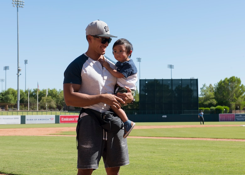 Staff Sgt. Joseluis Guerra, 56th Security Forces Squadron noncommissioned officer in charge of armory, and his son are recognized during a Major League Baseball Arizona Fall League game Oct. 6, 2019, at Camelback Ranch stadium in Phoenix.