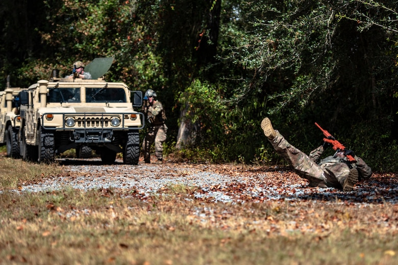 A simulated casualty, right, falls to the ground during a field convoy operation Oct. 8, 2019, at Moody Air Force Base, Ga. The field convoy operation gave 23d Security Forces Squadron Airmen an opportunity to improve the ability to shoot, move and communicate, ensuring the Airmen are properly trained and prepared to carry out their mission in a contested environment. (U.S. Air Force photo by Airman 1st Class Taryn Butler)