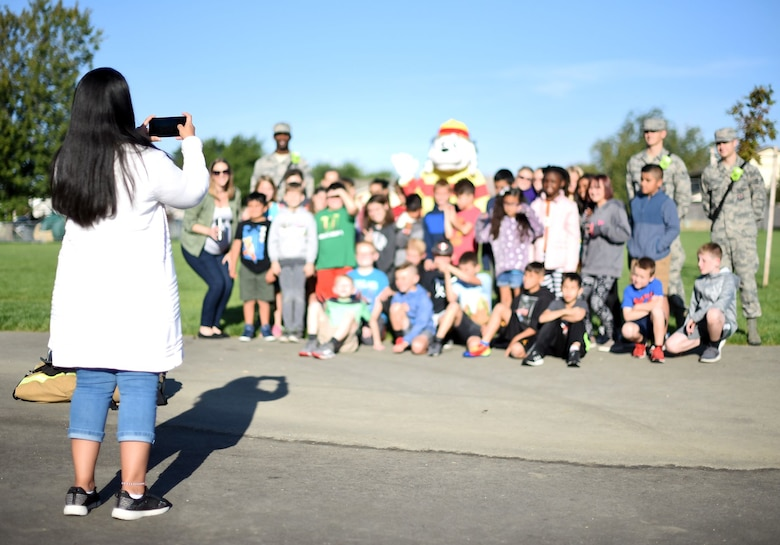 Grade school-aged children sit and stand among uniformed members of the Air Force along with Sparky the Fire Dog, a mascot for Fire Prevention Week, and pose for a photo taken by a smartphone.