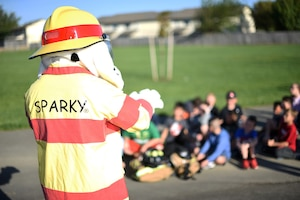 Sparky the Fire Dog, the mascot, communicates with grade school-aged children who are sitting. It is a sunny morning.