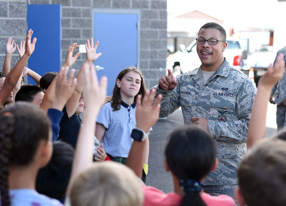 A uniformed member of the Air Force stands among grade school-aged children and look to be asking them a question. Many of the children's hands are up in gesture of a question or as a means of participation.
