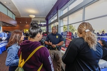 Joseph Carroll, Marine Corps Police Officer, speaks with three young women about career opportunities aboard Marine Corps Logistics Base Barstow during the Career and Education Expo at Barstow Community College, Barstow, Calif., Oct. 3.