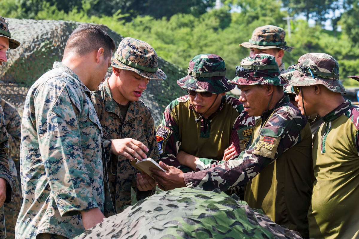 A group of U.S and Filipino troops look over a document.