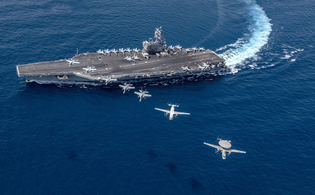 A group of aircraft fly in a line over a sailing aircraft carrier.