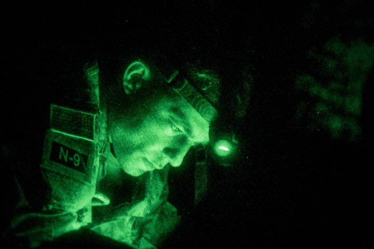 A soldier wearing a headlight is seen through night vision.