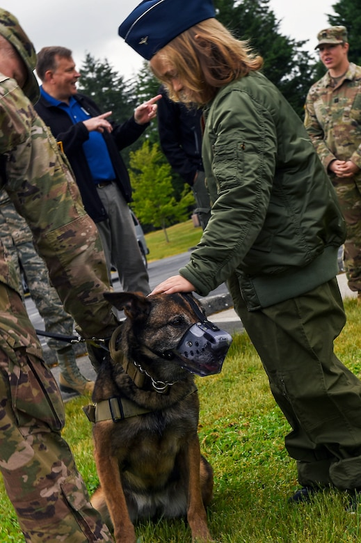 Declan Gaskill, Joint Base Lewis-McChord (JBLM) Pilot for a Day (PFAD) participant, right, meets a military working dog on JBLM, Wash., May 21, 2019. In addition to a military working dog demonstration, Declan's PFAD day itinerary also included train station, fire department, and air traffic control tower tours and a try in a C-17 flight simulator.