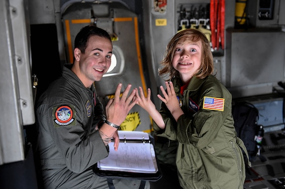 "Senior Airman Brennan Casey, 4th Airlift Squadron loadmaster, and Declan Gaskill, Joint Base Lewis-McChord (JBLM) Pilot for a Day (PFAD) participant, pose with the 4th Airlift Squadron ""four"" inside a C-17 Globemaster III on JBLM, Wash., May 21, 2019. When a child participates in the PFAD program, they and their family are inducted as honorary members of the 4th Airlift Squadron."