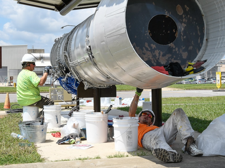 AEDC team members Jamie Elam, left, and Jonathan Finn, apply a fresh coat of paint Aug. 9 to a TF-30 engine on display in front of the Engine Test Facility at Arnold Air Force Base. The engine, tested in the ETF in the 1960s, was the first afterburner turbofan engine. The F-111 Aardvark, a multipurpose tactical fighter bomber retired from U.S. service in 1996, was powered by two TF-30 engines, and could fly at supersonic speeds. (U.S. Air Force photo by Jill Pickett) (This image has been altered by obscuring items for security purposes.)