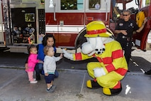 Children of the Child Development Center lined up to give Sparky, Fire Prevention mascot, a high-five during the Fire Department's visit to the CDC aboard Marine Corps Logistics Base Barstow, Calif., Oct. 9. (U.S. Marine Corps photo by Jack J. Adamyk)