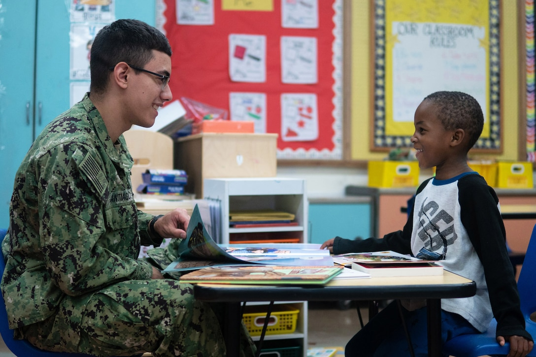 A sailor talks with a child across a table with books.