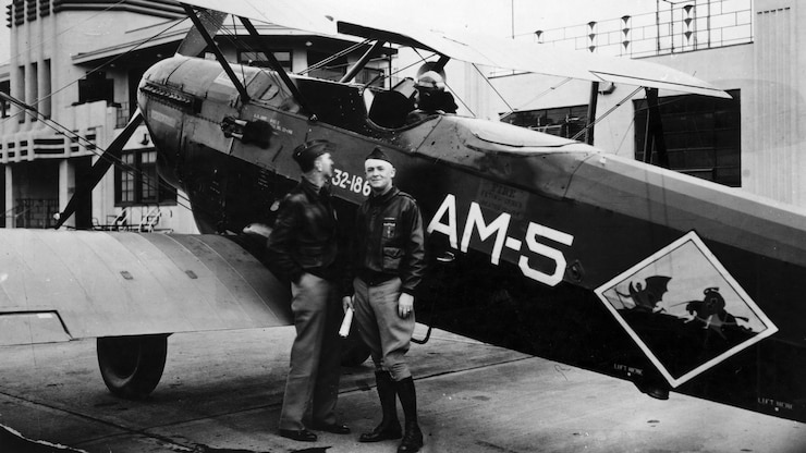 Two men stand in front of a prop aircraft.