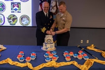 """As the oldest and youngest members, Joint Task Force Civil Support Command Surgeon U.S. Navy Capt. Bryan Schumacher (left) and U.S. Navy Hospital Corpsman 3rd Class Tyler Arentzen (right) cut the cake during the 244th Navy birthday celebration. The theme of this year's celebration, """"No Higher Honor,"""" originates from a quote by Lt. Cmdr. Robert Copeland, commanding officer of the World War II destroyer USS Samuel B. Roberts (DDE-413). (Official DoD photo by Mass Communication Specialist 3rd Class Michael Redd/RELEASED)"""