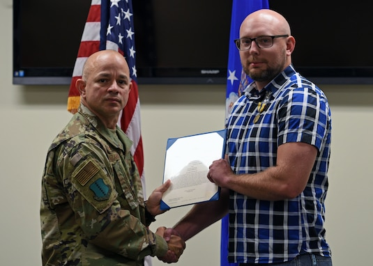U.S. Air Force Col. Andres Nazario, 17th Training Wing commander, presents Special Agent, Kyle Carter, with The Air Force Commendation Medal on Goodfellow Air Force Base, Texas, Oct. 9, 2019, for his acts of courage in providing first aid to victims of a stabbing at a local nightclub Sept. 12, 2019. Carter provided immediate first aid to the victims and briefed paramedics of the incident before the victims were transported to a local hospital. (U.S. Air Force photo by Airman 1st Class Robyn Hunsinger/Released)