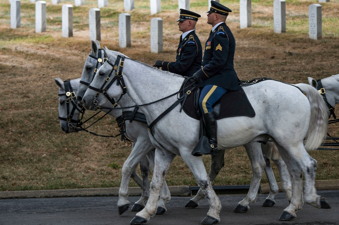 Soldiers on horseback proceed on a roadway past gravestones.
