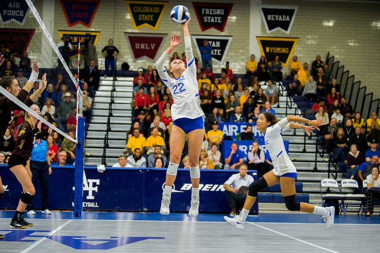 Two volleyball players jump in the air to spike a ball during a game while others look on.