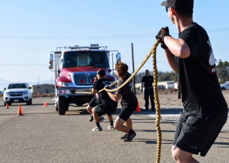 Service members pull a firetruck during the 2019 Fire Muster Challenge Oct. 10, 2019, at Vandenberg Air Force Base, Calif. Fire Prevention Week is observed annually during the week of October 9th to commemorate the Great Chicago Fire on October 8, 1871. Each year, firefighters from the installation provide lifesaving public education in an effort to drastically decrease casualties caused by fires. (U.S. Air Force photo by Airman 1st Class Aubree Milks)