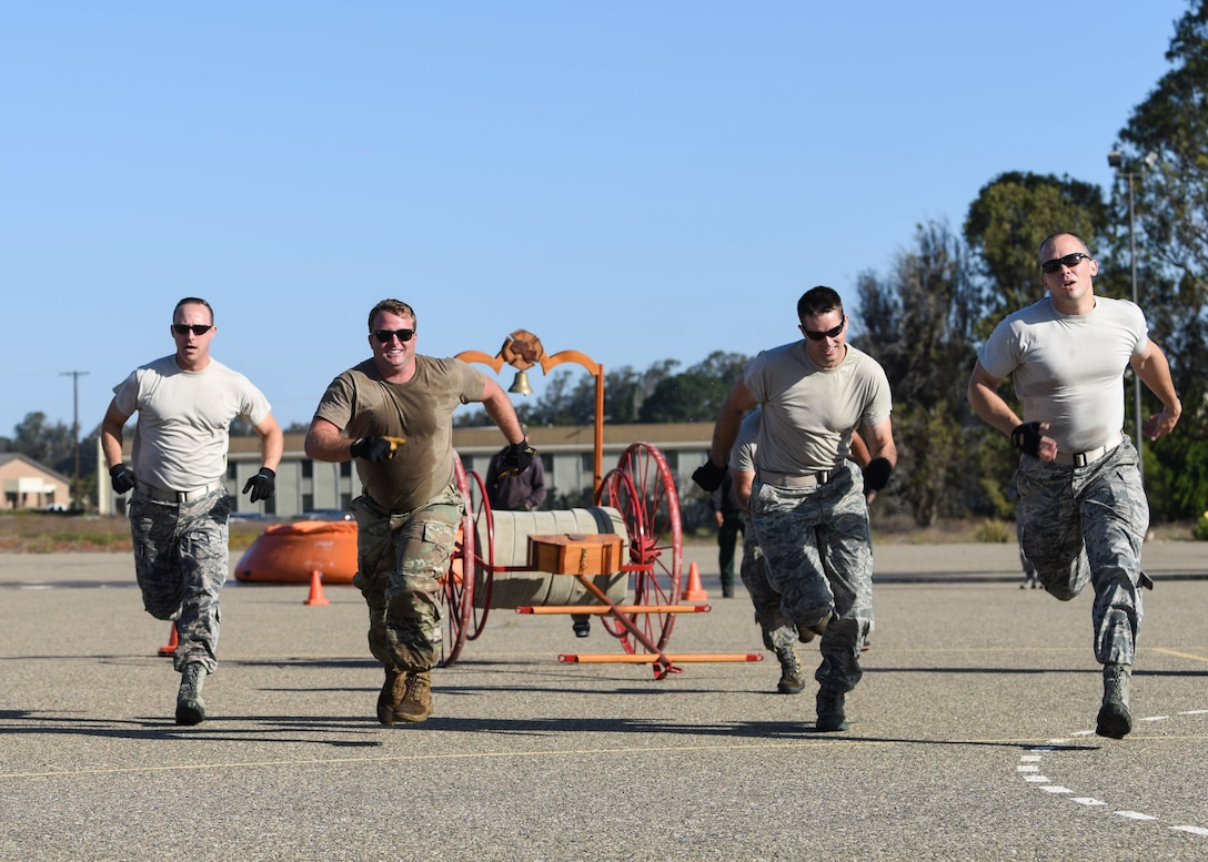 Service members run during the 2019 Fire Muster Challenge to commemorate Fire Prevention Week Oct. 10, 2019, at Vandenberg Air Force Base, Calif. During the event, five-member teams competed in the timed events to be the champion of the 2019 Fire Muster Challenge. (U.S. Air Force photo by Airman 1st Class Aubree Milks)