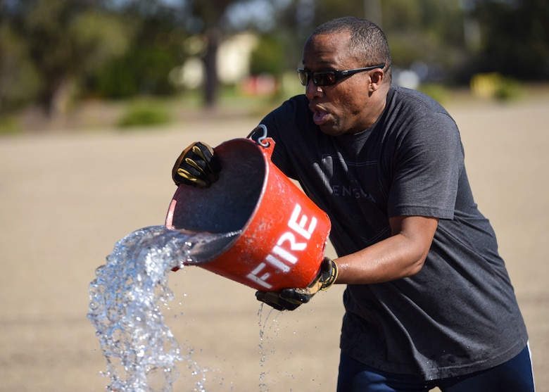 Senior Master Sgt. Curtis Brooks, 4th Space Launch Squadron superintendent, throws water in attempt to put out a house fire during the 2019 Fire Muster Challenge Oct. 10, 2019, at Vandenberg Air Force Base, Calif. More than 100 members from Vandenberg AFB gathered to participate and support this year's Fire Prevention Week. Out of the 15 teams, a five-member group from 30th Civil Engineer Squadron won the 2019 Fire Muster Challenge. (U.S. Air Force photo by Airman 1st Class Aubree Milks)