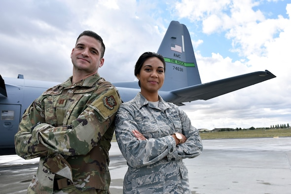 Airmen pose for a photo in front of a C-130.
